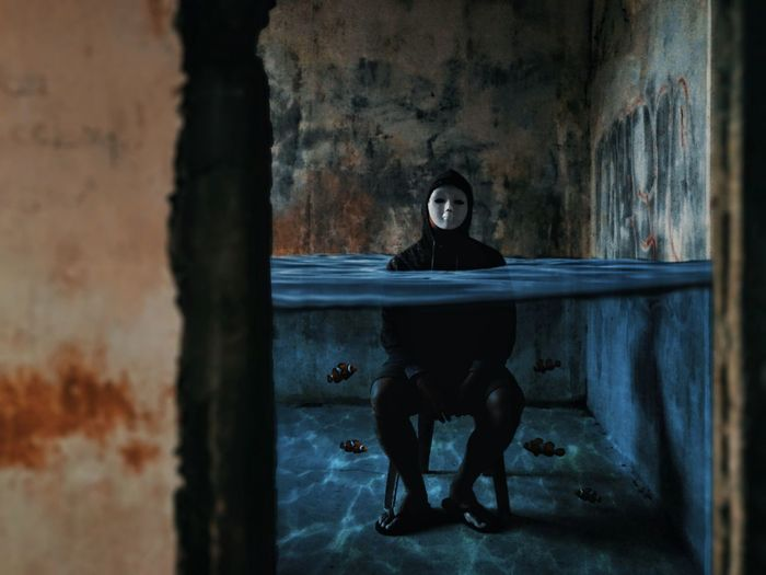 Full length portrait of woman sitting in abandoned building