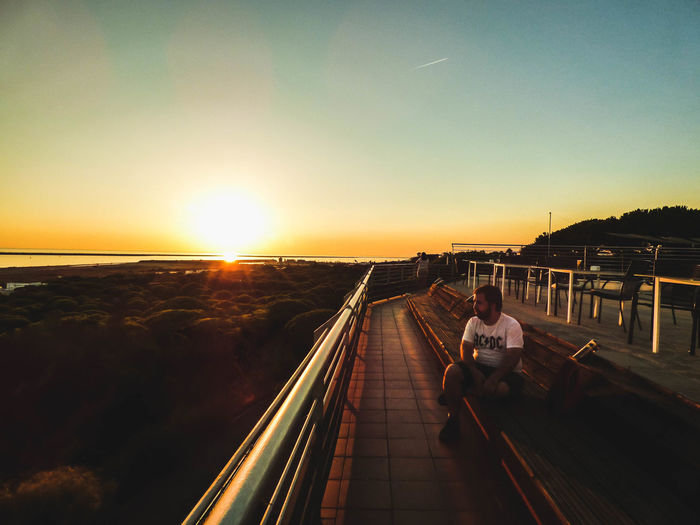 Rear view of man sitting on railing against sky during sunset