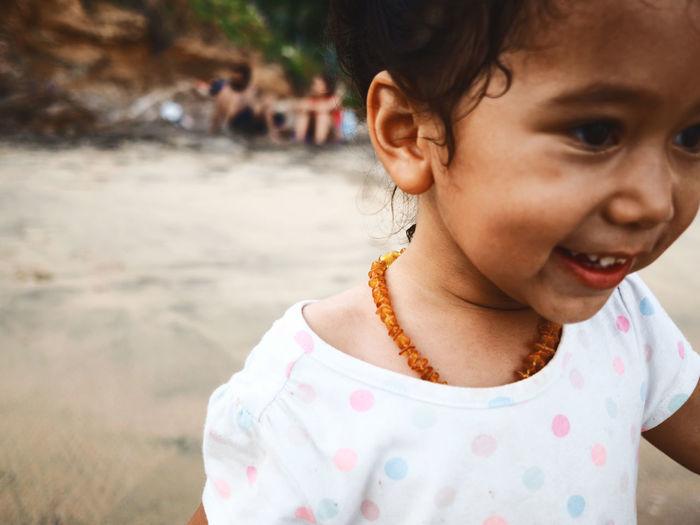 Close-up of smiling girl at beach