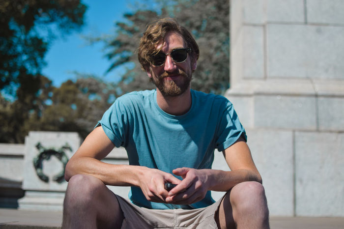 Nathan sat in front of the Edward VII monuments in Queen Victoria Gardens, Melbourne. Blue T Shirt Happy People Man Sunny Beard Blue Sky Casual Clothing Focus On Foreground Front View Happy Man Leisure Activity Lifestyles Man By Wall One Person Outdoors Portrait Real People Sat Down Sitting Smiling Sunglasses Sunny Day T-shirt Young Man Young Men