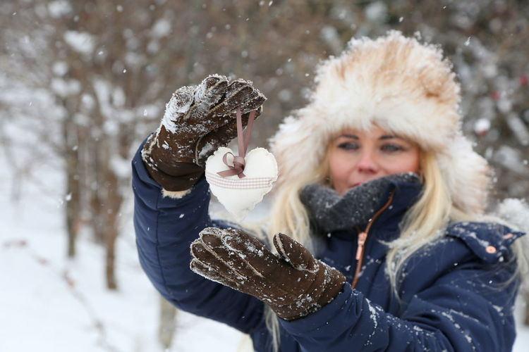 Woman wearing warm clothing while holding heart shape during winter