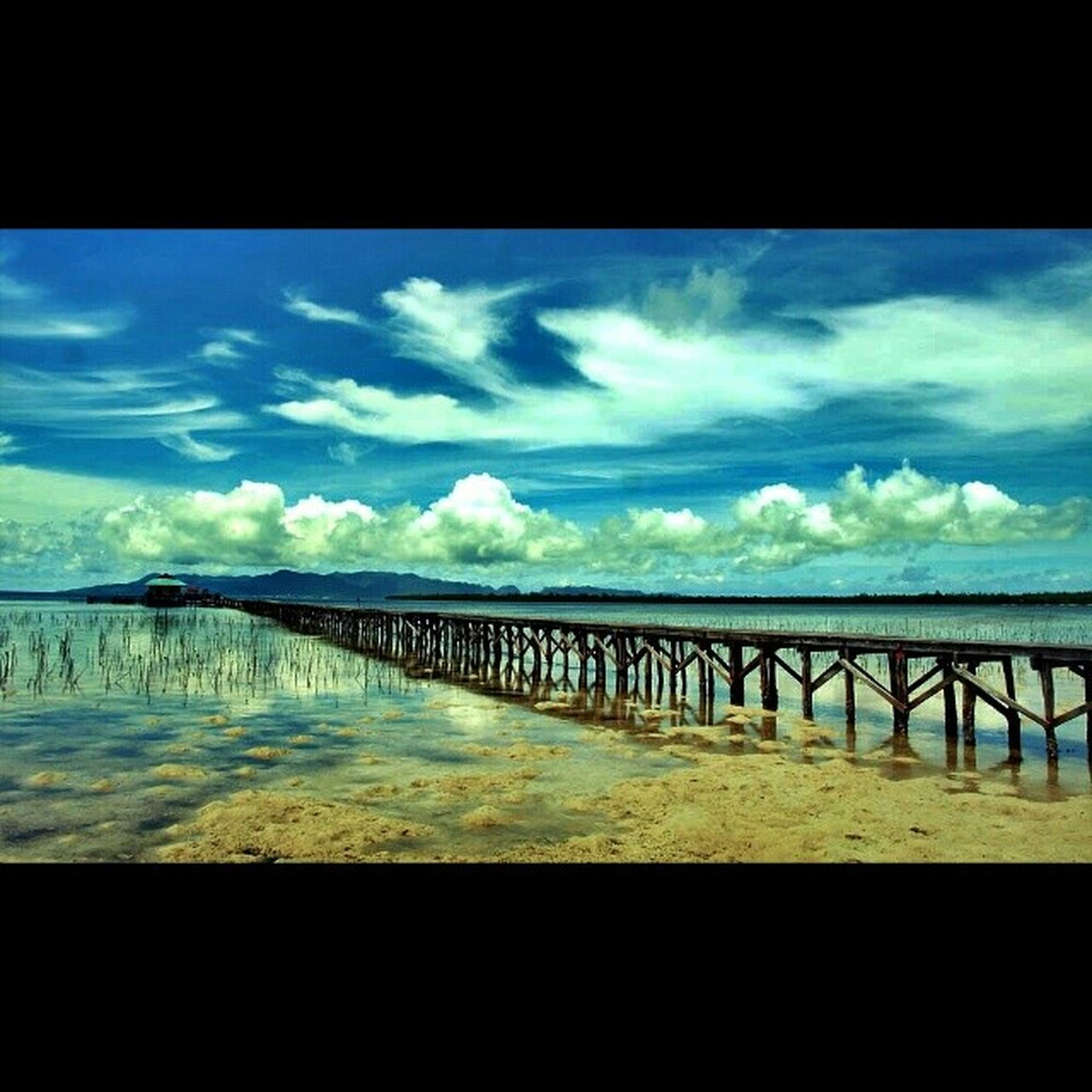 water, sky, sea, cloud - sky, scenics, tranquil scene, tranquility, cloud, cloudy, railing, pier, horizon over water, beauty in nature, nature, beach, blue, built structure, idyllic, auto post production filter, calm