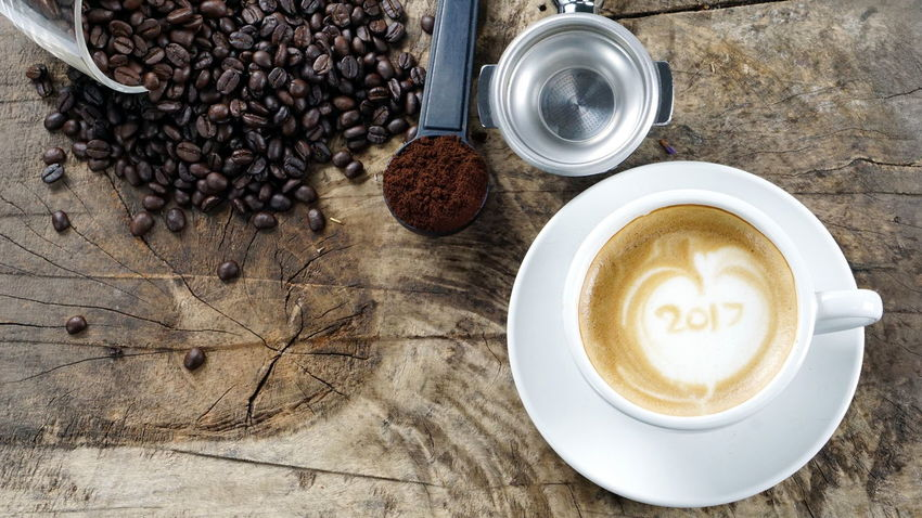 2017 Coffee Cup. A cup of latte, cappuccino or espresso coffee with milk put on a wood table with dark roasted coffee beans Aroma Bakery Beans Boiler Cafe Cappuccino Coffee Cookies Cream Cup Drink Espresso Fresh Headshot Latte Make Mashed Milk Morning Plate Pressure Roasted Robust Stream Table