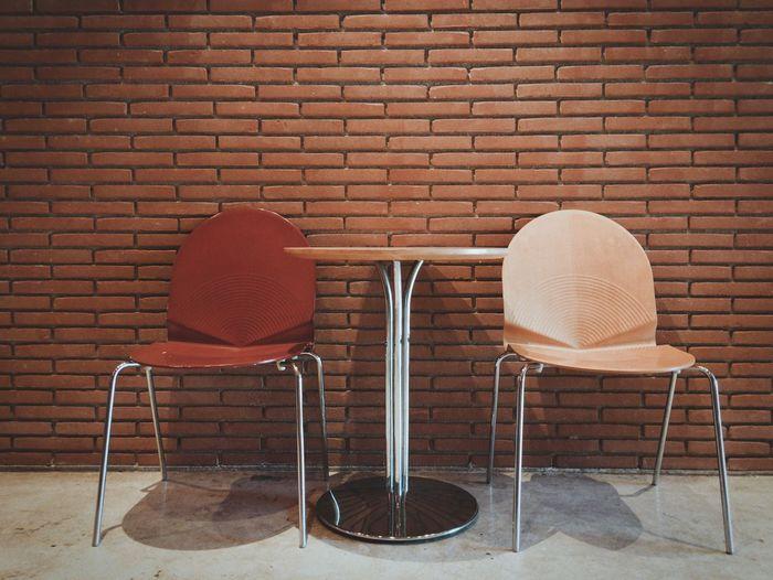 Empty chair against brick wall