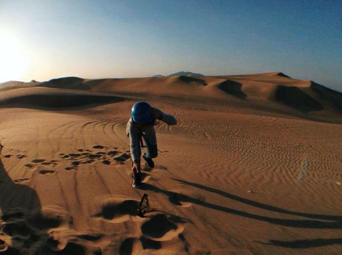 Boy reaching for eyewear on sand dune in desert against sky