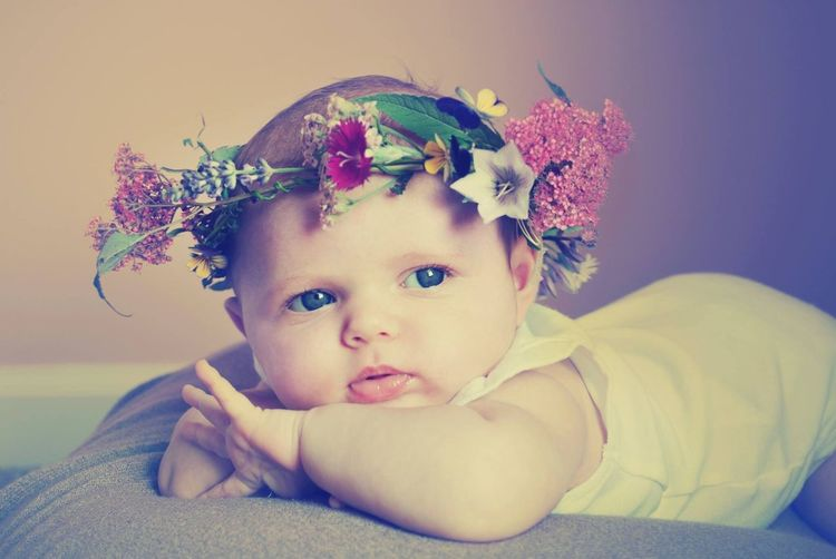 Close-Up Of Cute Toddler Wearing Flower Wreath Lying On Bed At Home