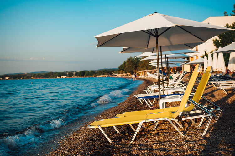 Lounge Chairs And Parasol At Beach Against Sky