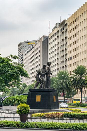 Statue against buildings in city against sky
