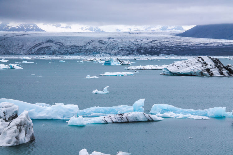 High angle view of icebergs in lake against cloudy sky