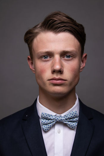Portrait of young man in a suit against gray background.