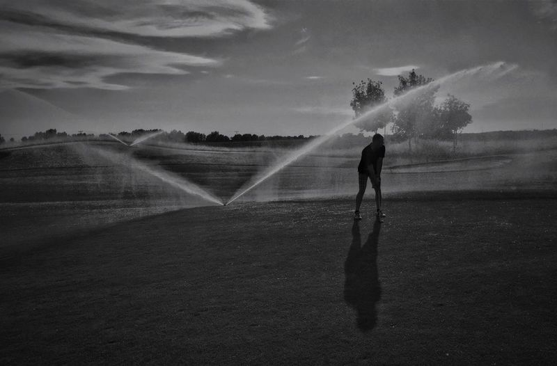 Man playing golf by fountain in park