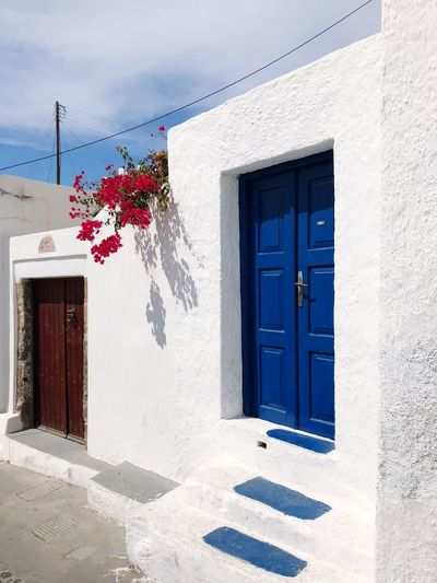 Picturesque Greek doors in the town of Megalochori on Santorini Santorini Caldera Megalochori EyeEm Selects Building Exterior Built Structure Architecture Building Window Day Residential District Nature Sunlight No People Hanging Shadow Entrance Outdoors Closed Blue House Door Sky Plant