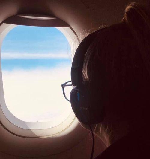 Portrait of man looking through airplane window
