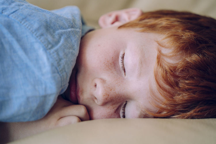 Close-up of boy sleeping on sofa