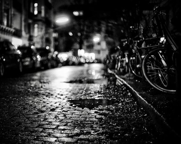 Wet Streets Dramatic Angles Black And White Transportation City Mode Of Transportation Night Wet Land Vehicle Street Architecture Direction No People The Way Forward Bicycle Rainy Season Outdoors Road Water Car Motor Vehicle Rain Illuminated The Street Photographer - 2018 EyeEm Awards