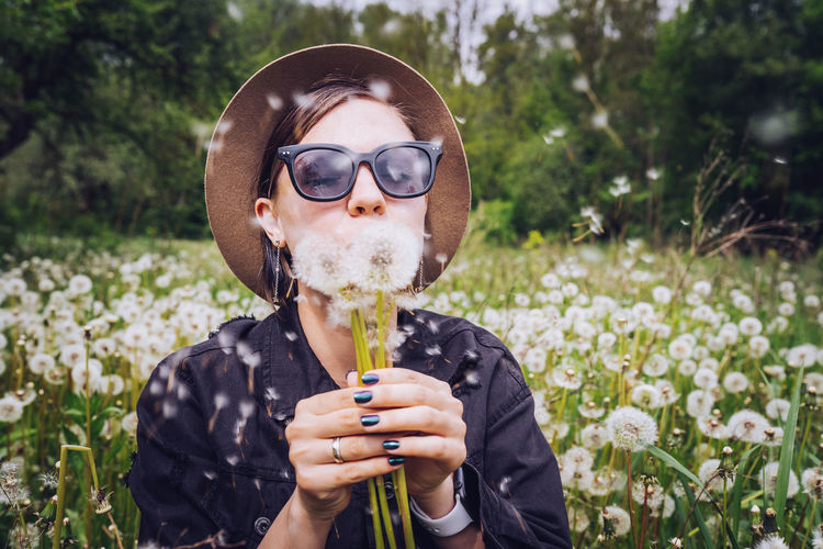 Young woman blowing dandelions at park