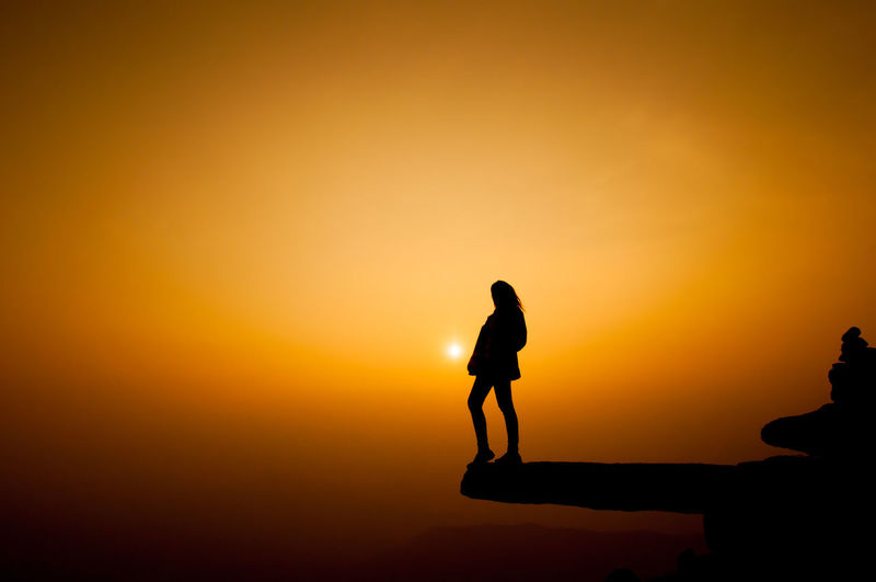 Silhouette woman standing on cliff against sky during sunset