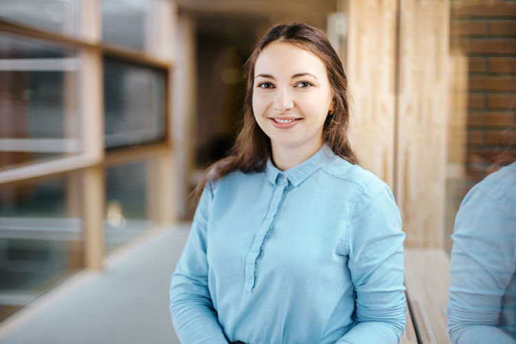 Portrait of happy young businesswoman standing at office corridor