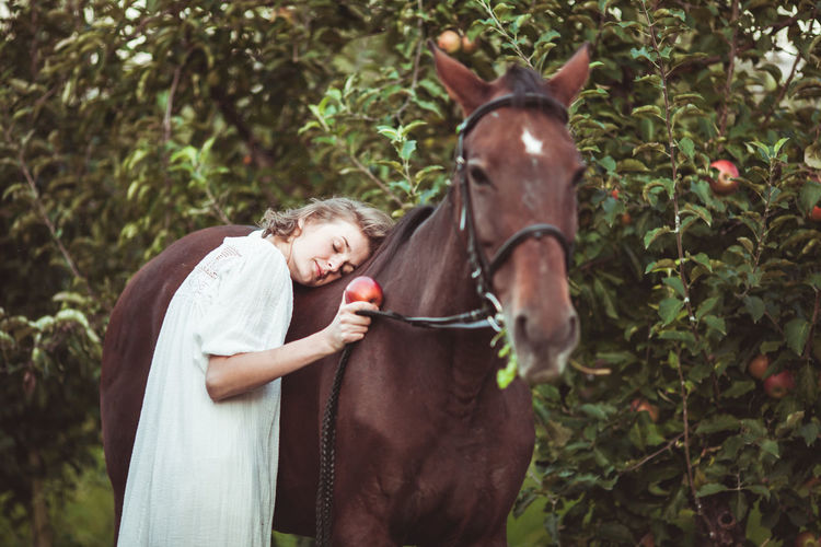 Woman leaning on horse in farm