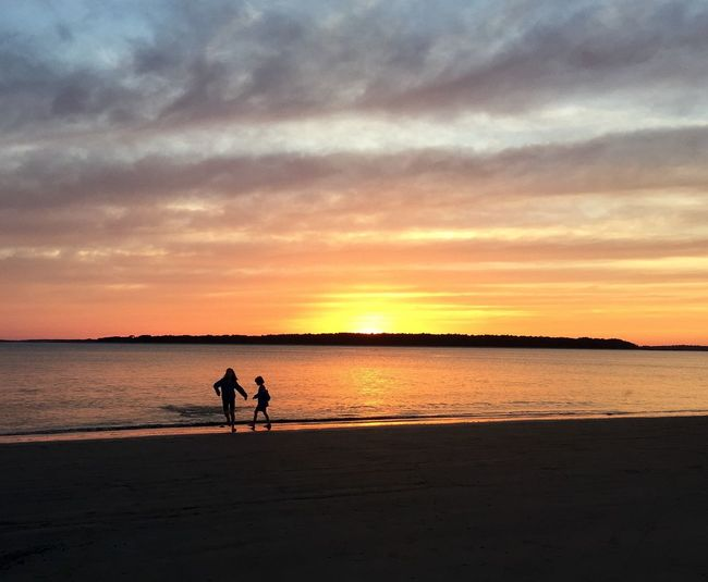 Silhouette of two children on beach at sunset