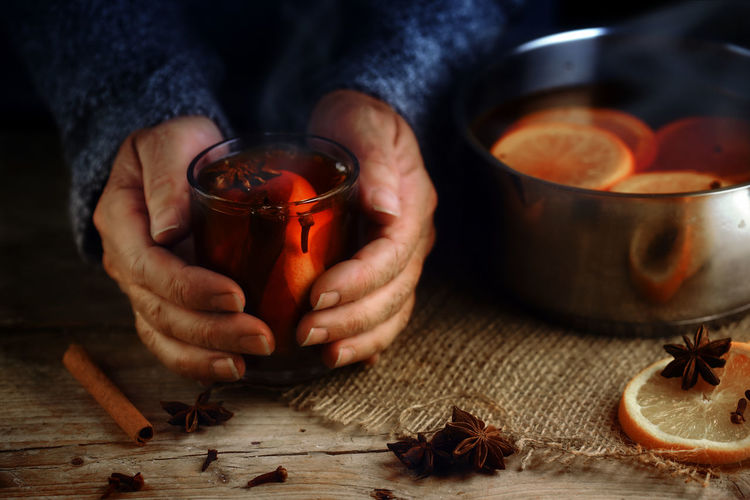 Hot Orange Red Rustic Tea Warming Winter Alcohol Cinnamon Day Drink Focus On Foreground Food And Drink Heat - Temperature Holding Human Hand Indoors  Mulled Wine People Pot Preparation  Slices Spices Traditional Wooden