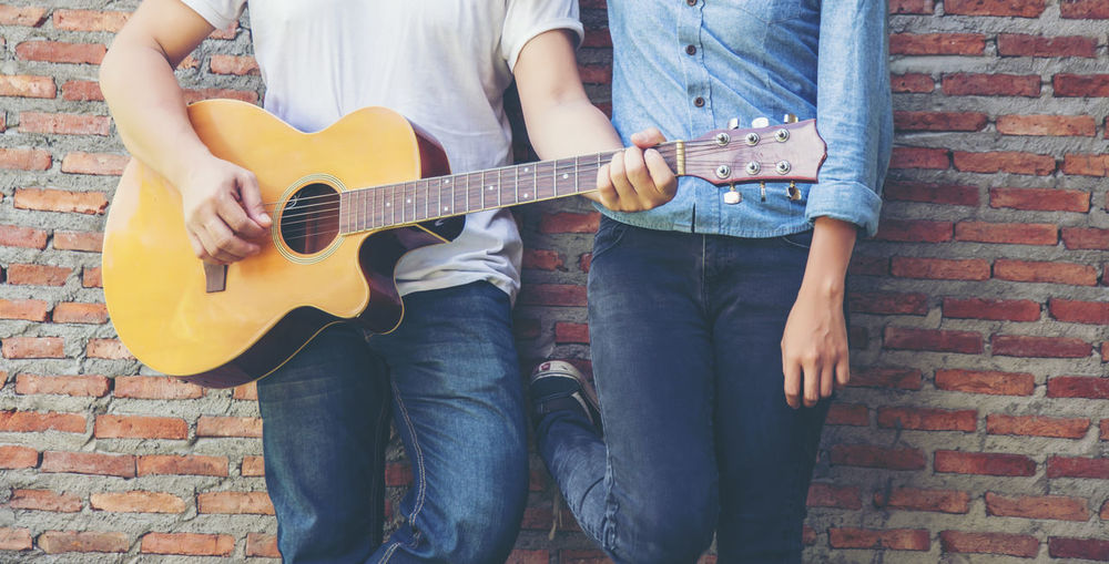 Midsection of man playing guitar with woman against brick wall