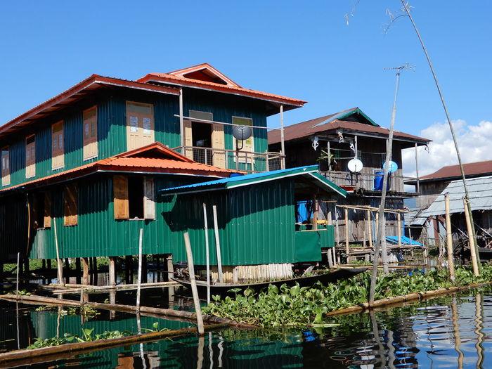 Houses by lake against buildings against clear sky
