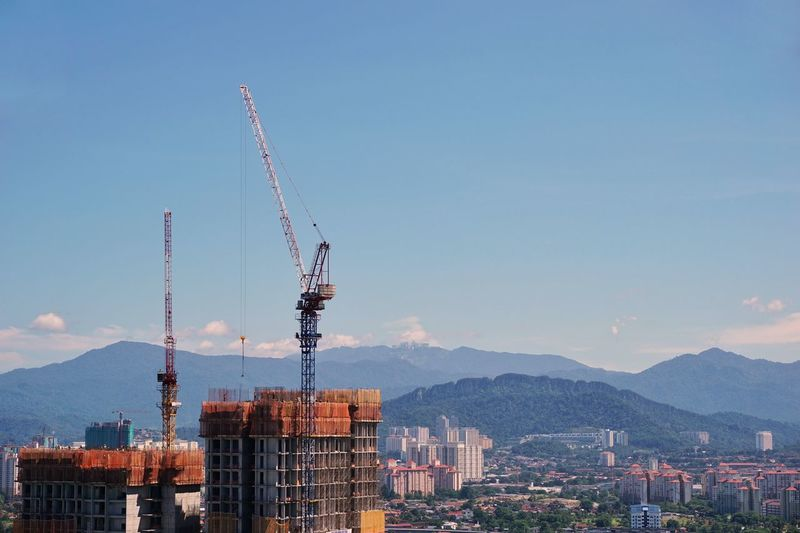 Cranes in city against clear sky