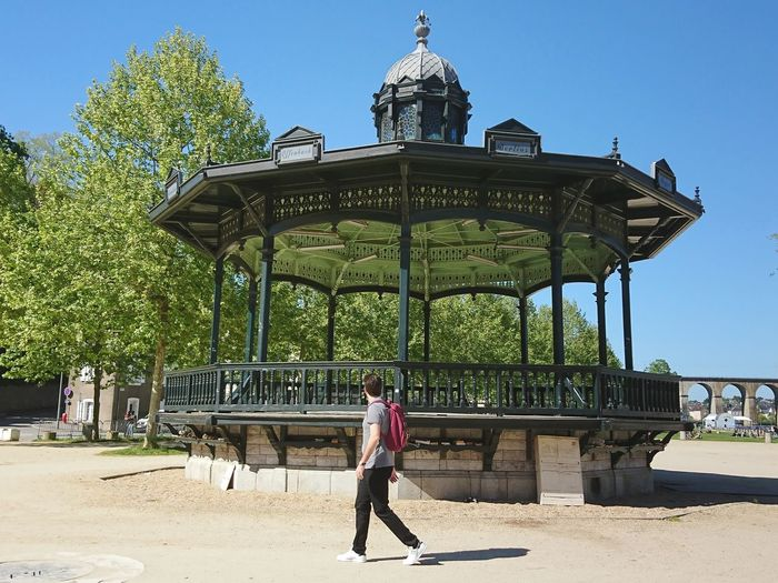 Full Length Side View Of Man Walking On Street By Gazebo During Sunny Day
