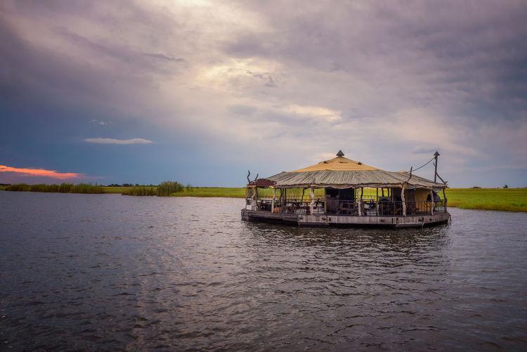 Stilt house on lake against sky