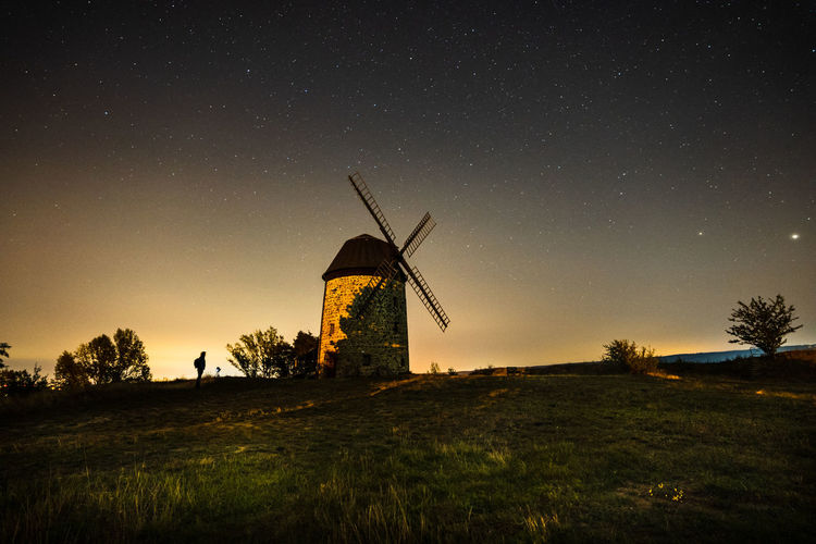 Traditional windmill on field against sky at night