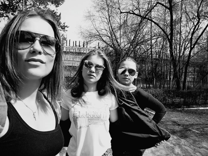 Portrait Of People Wearing Sunglasses While Standing Against Trees