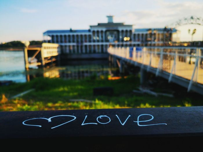 Close-up of text on bridge over river against sky