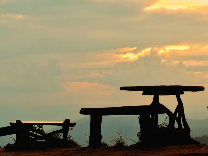 Silhouette bench on table against sky during sunset