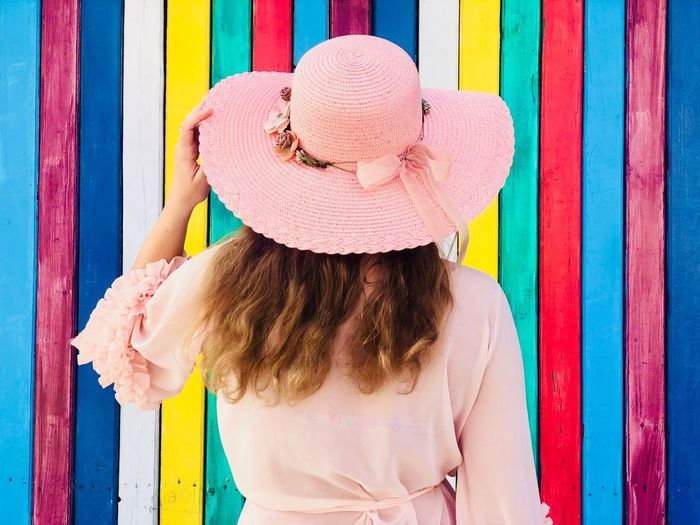 Back of woman wearing pink dress and pink hat standing in front of a colorful vertical striped wall Vibrant Color In A Row Bright Colors Bright Colors Colorful Wood - Material Wooden Building Striped Wall Striped Stripes Lines Vertical Wall Standing Waist Up Hairstyle Young Adult Hat Sun Hat Dress Fashionable Fashion Rear View Back Woman Day Summer