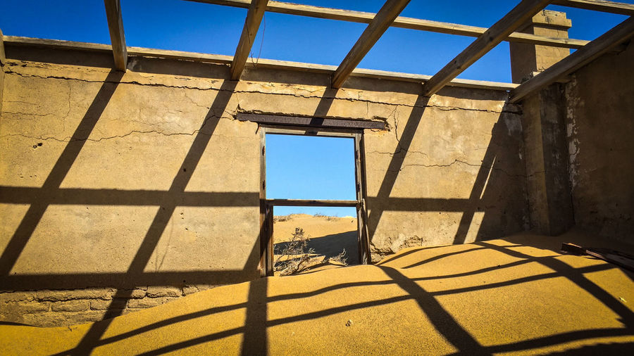 Ghost Town Kolmanskuppe in Lüderitz, Namibia Abandoned & Derelict Abandoned Buildings Abandoned House Abandoned Places Blue Sky Built Structure Decay Desert Deterioration Door Ghost Town Messy Ruin Sand Shadow Shadows Shadows & Lights Tourist Attraction  Window Window View