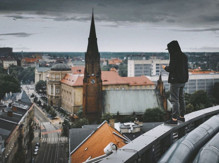 Hooded man standing on railing against cityscape