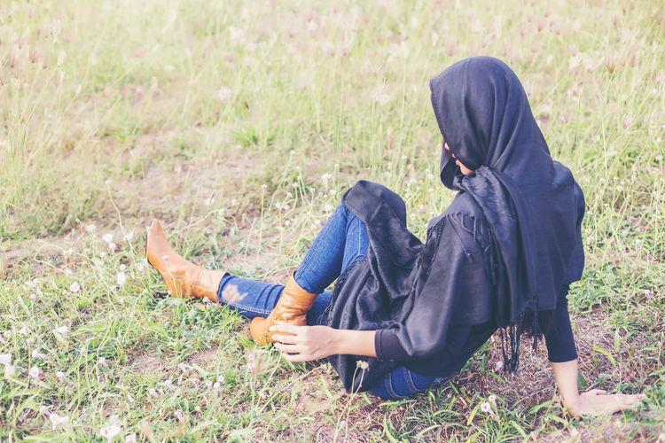 Woman wearing headscarf sitting on field