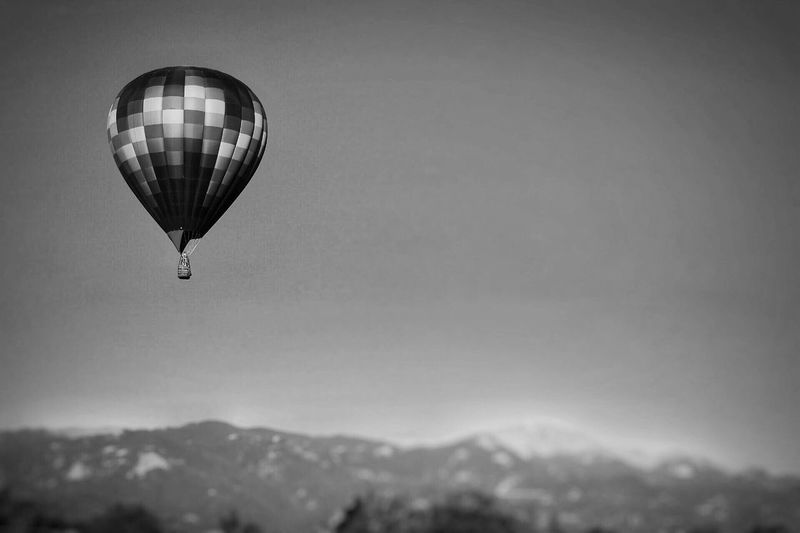 Black And White Friday Mid-air Mountain Sky Flying Hot Air Balloon Adventure Outdoors Clear Sky Nature No People Day Beauty In Nature Ballooning Festival