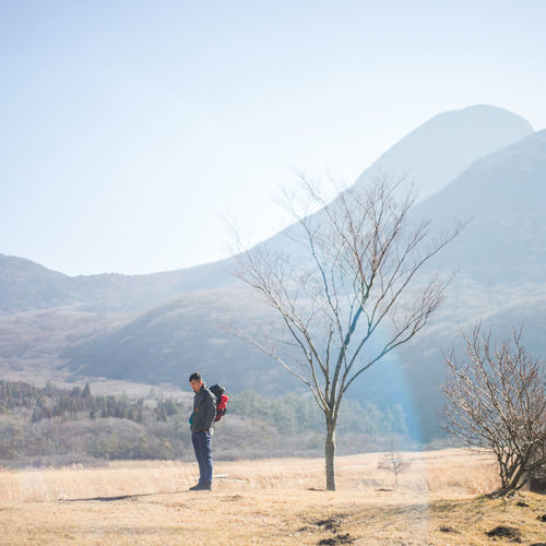 Side view of woman standing on field against mountain