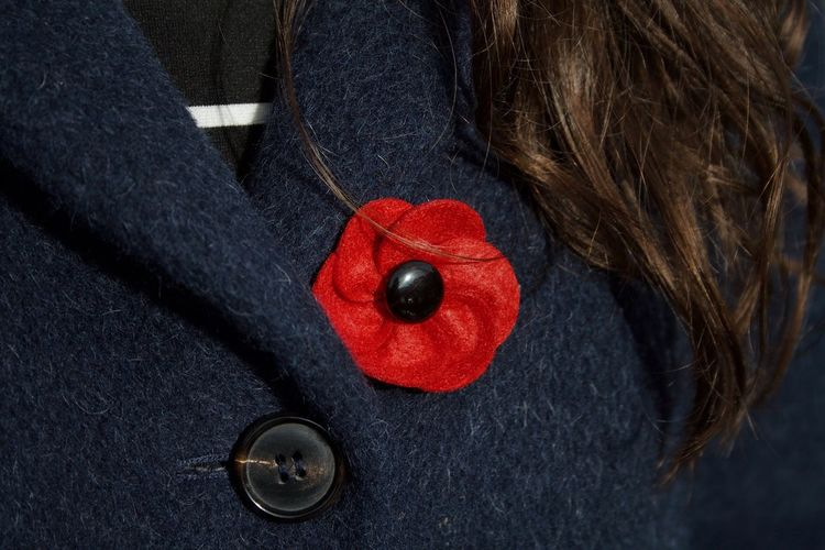 Close-up of red brooch on coat