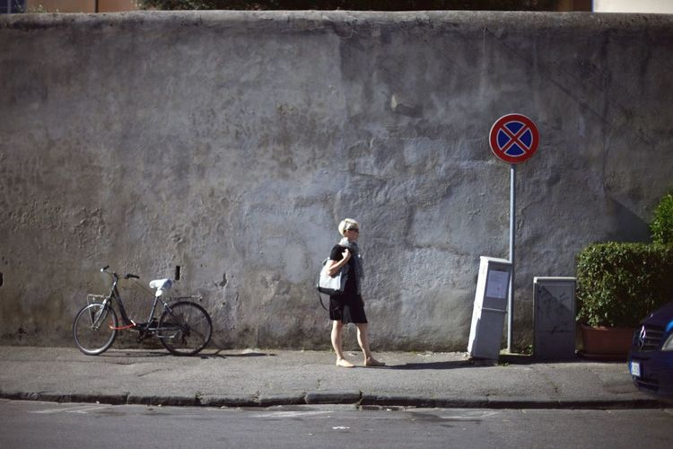 Woman standing by bicycle on footpath against retaining wall