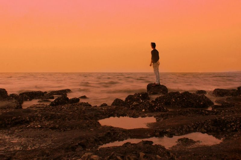 Rear View Of Man Standing On Rock At Seashore Against Sky During Sunset