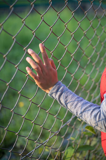 Midsection Of Person Touching Chainlink Fence