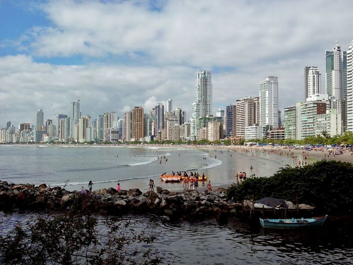 Panoramic view of sea and cityscape against sky