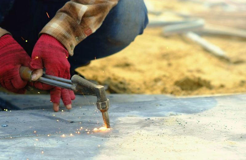 Cropped hands of manual worker welding metal at construction site