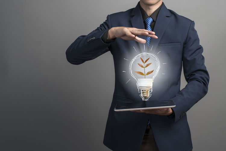 Midsection of man holding light bulb against white background