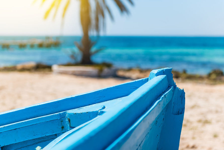 Front of a blue wooden boat on a sandy beach by the sea Beach Blue Day Focus On Foreground Holiday Horizon Horizon Over Water Land Nature No People Outdoors Sand Scenics - Nature Sea Sky Tranquil Scene Tranquility Trip Tropical Climate Turquoise Colored Water
