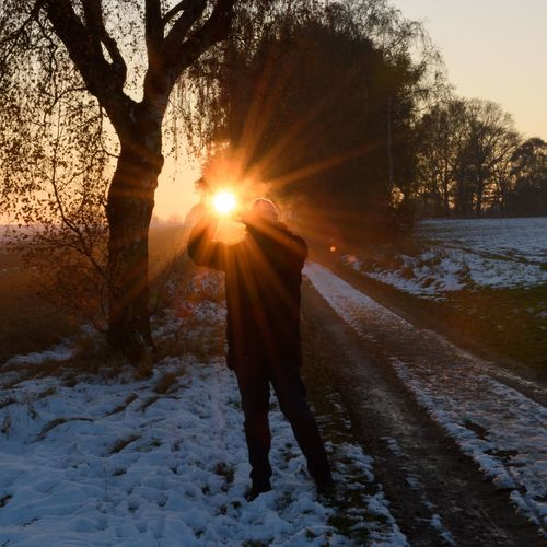Man walking on snow covered tree during sunset