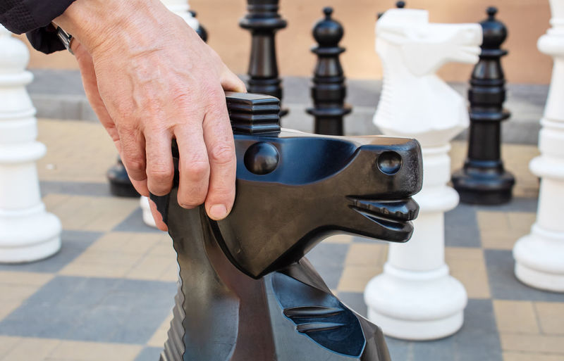 Close-up of hands holding large chess piece